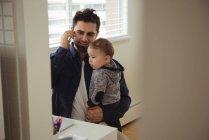 Padre che parla al cellulare mentre tiene in braccio il bambino a casa — Foto stock