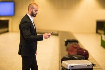 Businessman using mobile phone near baggage claim area at airport — Stock Photo