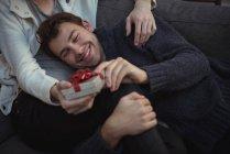 Primer plano de feliz pareja gay celebración de regalo festivo - foto de stock