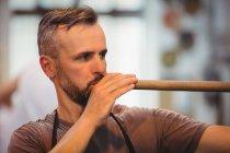 Стеклодув продувает трубу на стекольном заводе — стоковое фото