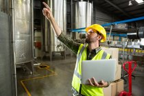 Male worker pointing up while holding laptop in factory — Stock Photo