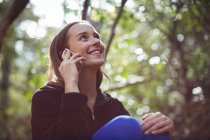 Happy woman talking on mobile phone in forest — Stock Photo
