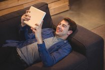Smiling man lying on sofa using digital tablet in living room at home — Stock Photo