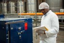 Серьёзные машины для проверки мужчин на соковом заводе — стоковое фото