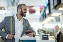 Улыбающийся бизнесмен, стоящий у стойки регистрации с паспортом и посадочным талоном в аэропорту — стоковое фото