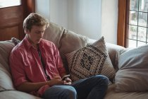 Man sitting on sofa using a mobile phone in living room — Stock Photo