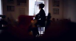 Задній вид жінка дивлячись через вікно в кафе — стокове фото