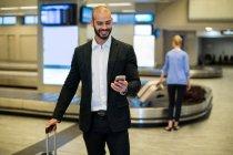 Empresário de pé com bagagem usando telefone celular na área de espera no terminal do aeroporto — Fotografia de Stock