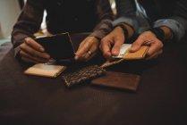 Artesãos discutindo sobre uma folha de couro em oficina — Fotografia de Stock