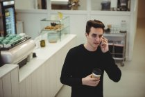 Man talking on his mobile phone while holding a coffee cup in coffee shop — Stock Photo