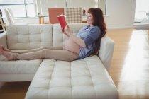 Вагітна жінка читання книги на дивані у вітальні на дому — стокове фото