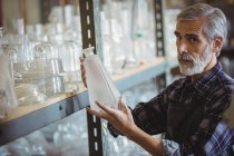 Retrato do soprador de vidro examinando objetos de vidro na fábrica de sopro de vidro — Fotografia de Stock