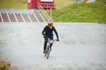 Cyclist riding BMX bike in skatepark — Stock Photo