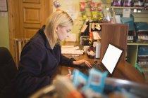 Femme utilisant un ordinateur portable et l'écriture sur le bloc-notes dans le bureau — Photo de stock
