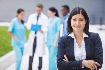 Портрет улыбающейся женщины-врача, стоящей со скрещенными руками в помещении больницы — стоковое фото