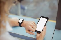Hands of businesswoman using mobile and checking time at counter in cafeteria — Stock Photo
