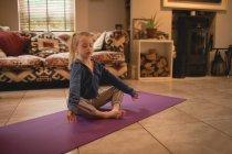 Mädchen macht Yoga im Wohnzimmer zu Hause — Stockfoto