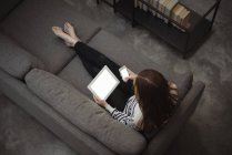Overhead view of relaxing woman using mobile phone and digital tablet on sofa at home — Stock Photo