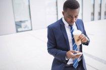 Uomo d'affari in possesso di tazza di caffè usa e getta e utilizzando il telefono cellulare al di fuori dell'edificio per uffici — Foto stock