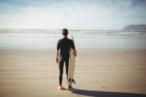 Вид сзади серфингиста, стоящего с доской для серфинга на пляже — стоковое фото