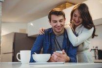 Casal usando celular enquanto tomando café na cozinha em casa — Fotografia de Stock
