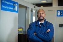 Portrait d'un agent de sûreté de l'aéroport debout les bras croisés dans un aérogare — Photo de stock