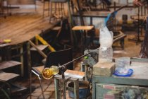 Плавленое стекло на трубе на мраморном столе на стеклодувном заводе — стоковое фото