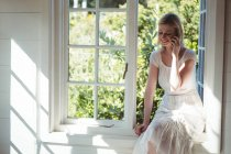 Beautiful woman talking on mobile phone at home — Stock Photo