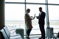 Gente de negocios usando teléfono móvil y tableta digital en el aeropuerto - foto de stock