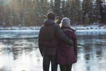 Rear view of romantic couple standing by river in winter — Stock Photo