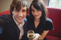 Couple holding drink and taking a selfie in restaurant — Stock Photo