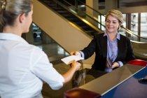 Бізнес-леді показ посадковий талон в на стійці реєстрації в аеропорту — стокове фото
