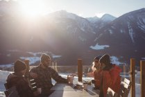 Skiers interacting with each other while having drinks in ski resort — Stock Photo