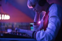 Female dj listening to headphones while playing music in bar — Stock Photo