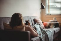 Woman lying on sofa using mobile phone in living room at home — Stock Photo