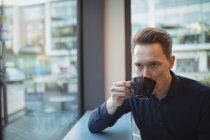 Мужчина-руководитель пьет кофе за стойкой в столовой — стоковое фото