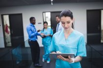 Beautiful nurse using digital tablet in hospital corridor — Stock Photo
