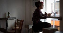 Donna sorridente che utilizza il telefono cellulare in caffè — Foto stock