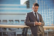 Businessman listening to music and using mobile phone near office building — Stock Photo