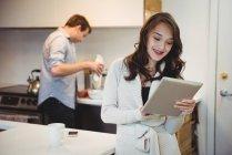 Donna che utilizza tablet digitale mentre l'uomo lavora in background in cucina — Foto stock
