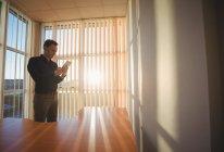 Ejecutivo masculino usando tableta digital cerca de persianas de ventana en la oficina - foto de stock