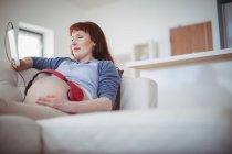 Femme enceinte avec écouteurs sur le ventre relaxant sur le canapé dans le salon — Photo de stock