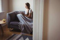 Femme utilisant tablette numérique sur canapé dans le salon — Photo de stock