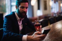 Businessman using mobile phone with glass of red wine in hand at bar — Stock Photo
