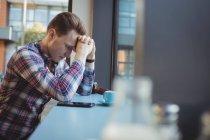 Homme bouleversé assis avec les mains sur le front dans un café — Photo de stock