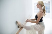Ballerina stretching on a barre while practicing ballet dance in the studio — Stock Photo