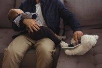 Sección media del padre sosteniendo a su bebé durante el uso de tabletas digitales en sofá - foto de stock