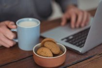 Primer plano de galletas en un tazón, hombre sosteniendo la taza de café mientras usa el ordenador portátil - foto de stock
