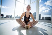 Ballerina stretching on the floor at studio — Stock Photo