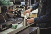 Mann gießt in Kaffeehaus Milch in Schaumkrug — Stockfoto